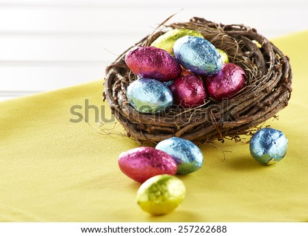 Chocolate eggs in nest on white  - stock photo