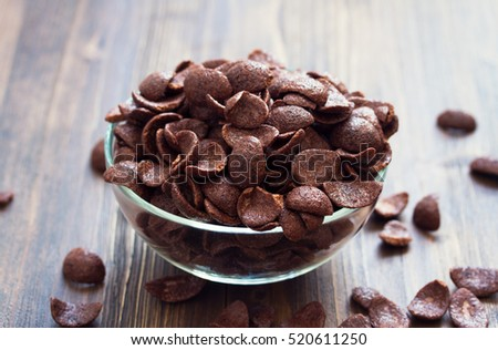 chocolate flakes on bowl on brown background