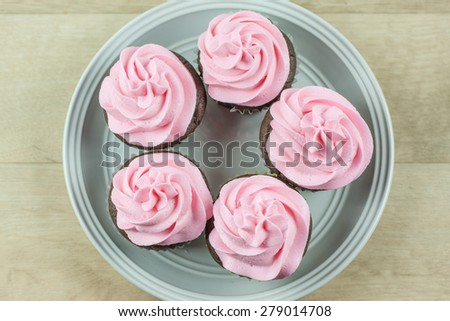 Chocolate flavored cupcakes frosted with pink butter cream frosting. - stock photo