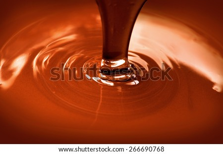 Chocolate flow. Close up of liquid hot chocolate pouring closeup. Chocolate swirl - stock photo