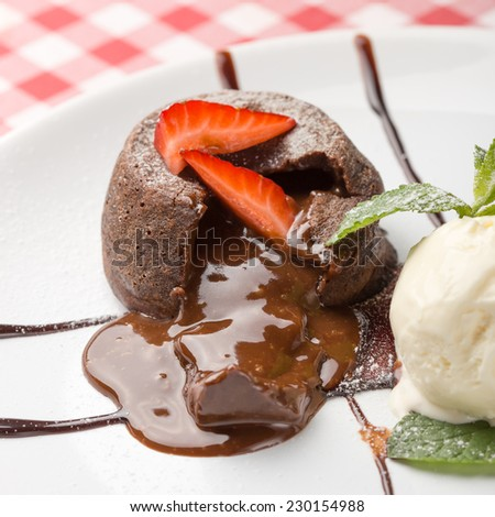 Chocolate fondant lava cake decorated with strawberries and vanilla ice cream on the table. Close up - stock photo