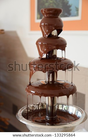 Chocolate fondue fountain with marshmallow being dipped. - stock photo