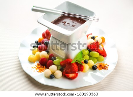 Chocolate fondue with fresh fruits and berries  - stock photo