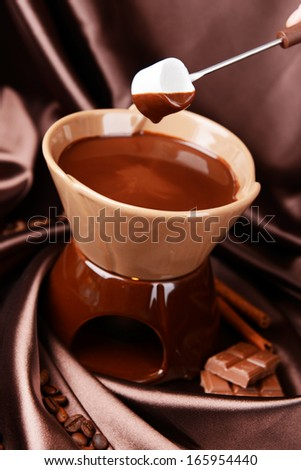 Chocolate fondue with marshmallow candies, on brown background - stock photo