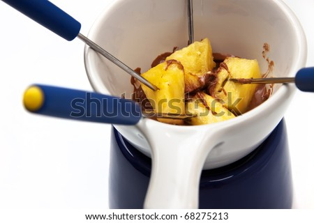 Chocolate fondue with pineapple pieces - stock photo