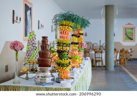 Chocolate fountain and palm-tree from fruits at wedding reception. - stock photo