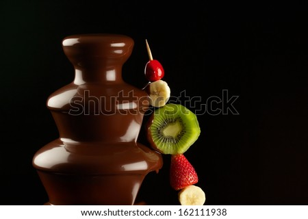 Chocolate fountain with fruits - stock photo