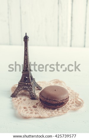 Chocolate French macaroons and Eiffel tower. Selective focus. Toning. Retro style.