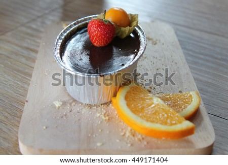 Chocolate frosted cupcake with strawberry and cape gooseberry topping. - stock photo