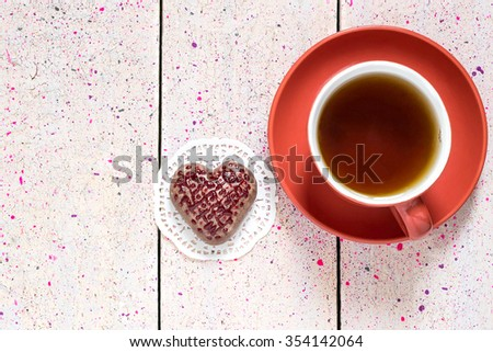 Chocolate gingerbread with frosting in the shape of a heart and tea in the red cup and saucer for Valentines day - stock photo