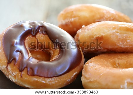 Chocolate glazed donuts background image. Macro with shallow dof. - stock photo