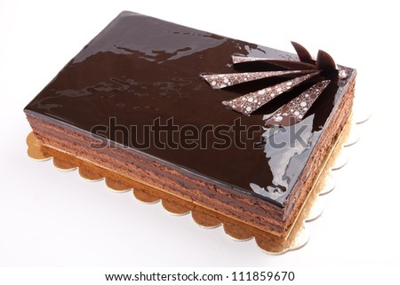 Chocolate glossy dark Cake on white stuffed with nuts - stock photo