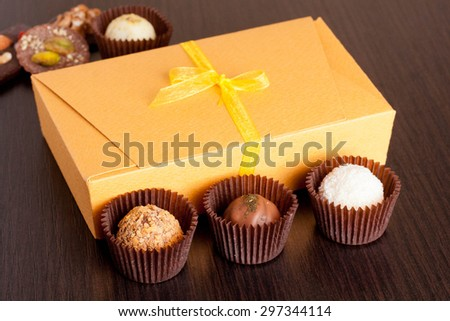 Chocolate handmade candies on a black table. Chocolate box, close up - stock photo