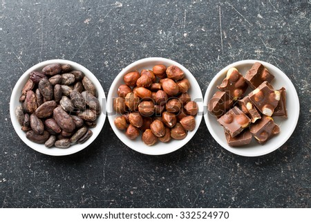chocolate, hazelnuts and cocoa beans on kitchen table - stock photo