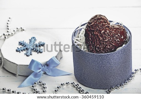 Chocolate heart in a gift box with a bow on a light wooden background - stock photo