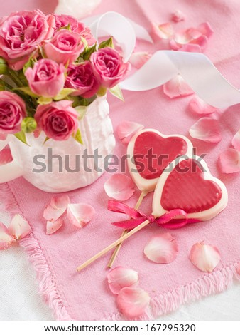 Chocolate heart lollipops with pink roses, selective focus - stock photo