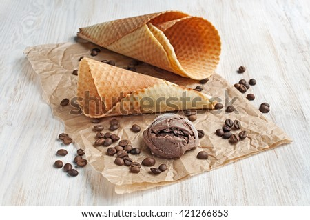 Chocolate ice cream and waffle cone on parchment paper