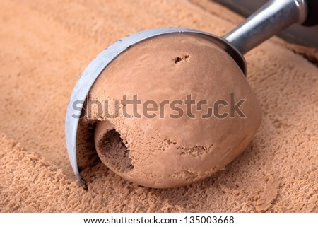 Chocolate ice cream scooped out of container. - stock photo