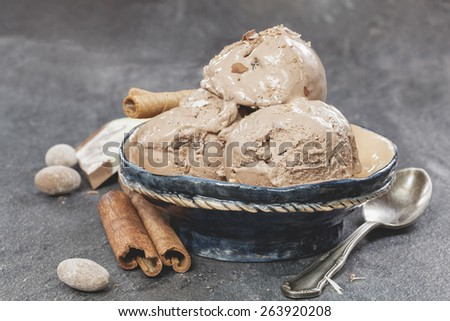 Chocolate ice cream. Scoops of chocolate ice cream with the spoon over dark granite table. Macro photograph with shallow depth of field.  - stock photo