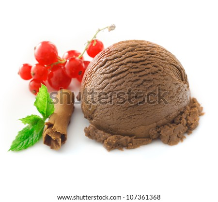 Chocolate icecream with redcurrants and a coiled shaving of milk chocolate with a fresh green mint leaf - stock photo