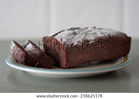 Chocolate Loaf cake on a plate in front of a white background. - stock photo