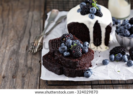 Chocolate loaf cake sliced decorated with frosting and berries - stock photo