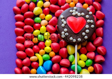 Chocolate lollipop with heart jelly on arranged colorful candies - stock photo