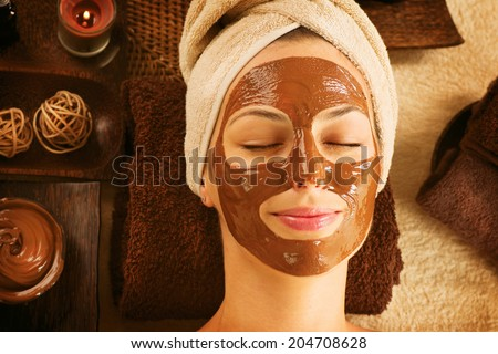 Chocolate Luxury Spa. Facial Mask. Spa therapy for young woman with cosmetic mask at beauty salon. Day spa treatment - stock photo