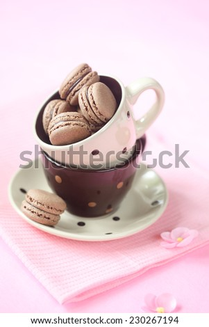 Chocolate Macarons in a polka dot tea cup, on a pink napkin and pink background. - stock photo