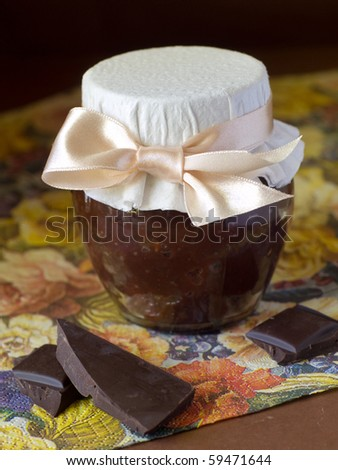 Chocolate marmalade with ribbon on floral napkin - stock photo