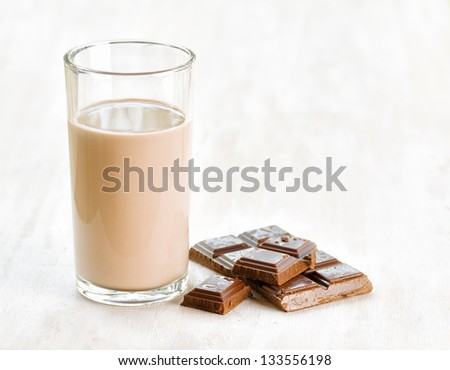Chocolate milk and chocolate on white wooden table. - stock photo