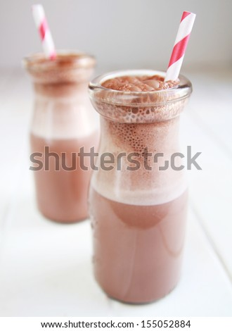 Chocolate milk in a bottle with red ribbon and red straw - stock photo