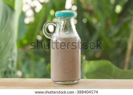 Chocolate milk in glass bottle on garden background - stock photo