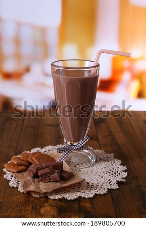 Chocolate milk in glass, on wooden table, on bright background - stock photo