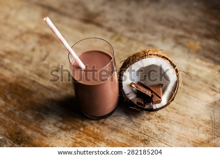 Chocolate milk protein shake with colored striped straw and coconut   - stock photo