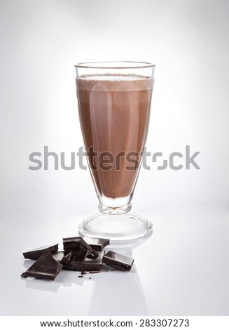 Chocolate milkshake in a tall glass with chocolate chips