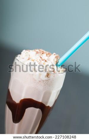 chocolate milkshake on blue background - stock photo