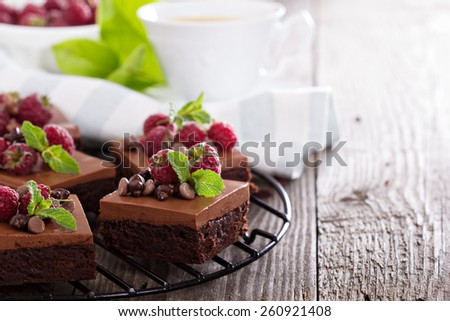 Chocolate mousse brownies with raspberry on a cooling rack - stock photo
