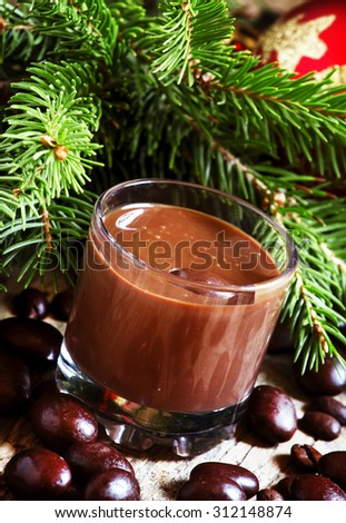 Chocolate mousse, candy, coffee beans with fir branches on a wooden background, selective focus