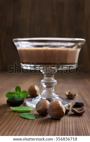 Chocolate mousse dessert with mint and hazelnuts on wooden