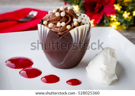 Chocolate mousse in tulip shaped chocolate cup with fresh whipped cream and raspberry sauce sitting on white plate with holiday centerpiece in background