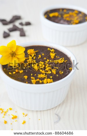 chocolate mousse in two tins of white, sprinkled with orange zest and decorated with a yellow flower on a wooden table, near the spill zest and slices of chocolate, vertical frame