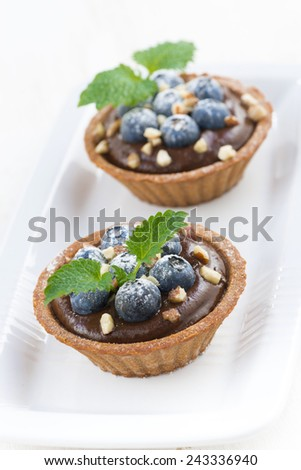 chocolate mousse with blueberries, nuts and mint in tartlets, vertical, top view - stock photo