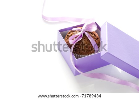 Chocolate muffin, tied with purple ribbon in a gift box on white background