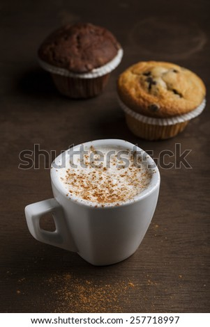 Chocolate muffin with a cup of coffee on a wooden background