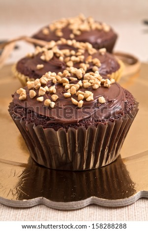 chocolate muffin with chocolate sauce and hazelnuts - stock photo