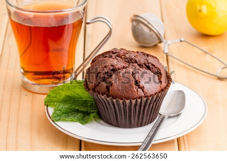 chocolate muffin with cup of tea on wooden background  - stock photo