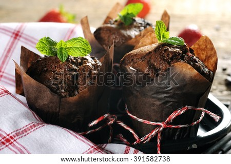 chocolate muffin with mint leaves on a wooden table - stock photo