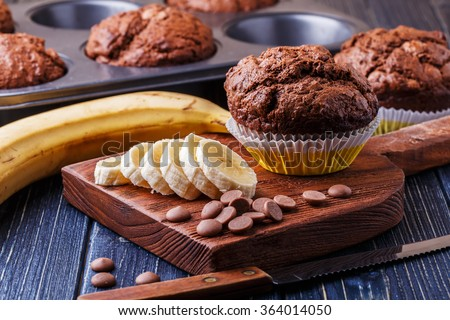 Chocolate muffins with banana on dark background, selective focus. - stock photo