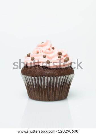 Chocolate muffins with icing and colorful sprinkles - stock photo